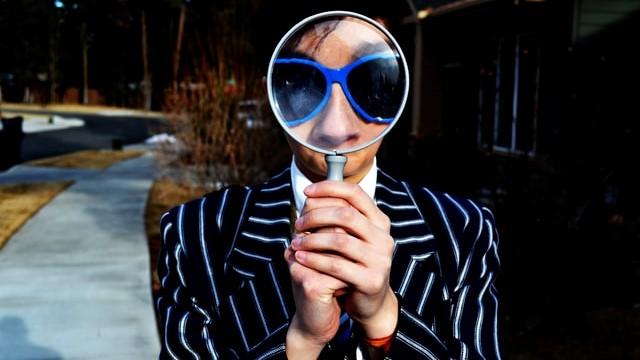 En person ser gjennom et forstørrelsesglass