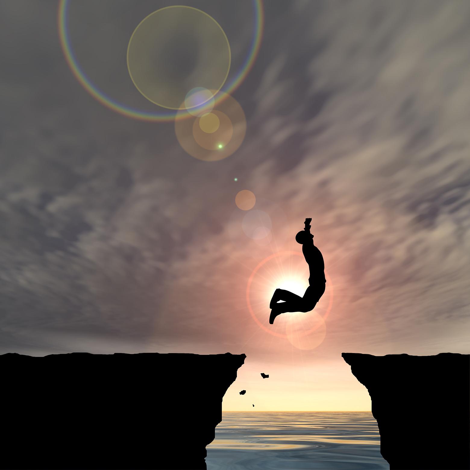 En person hopper fra et fjell til et annet